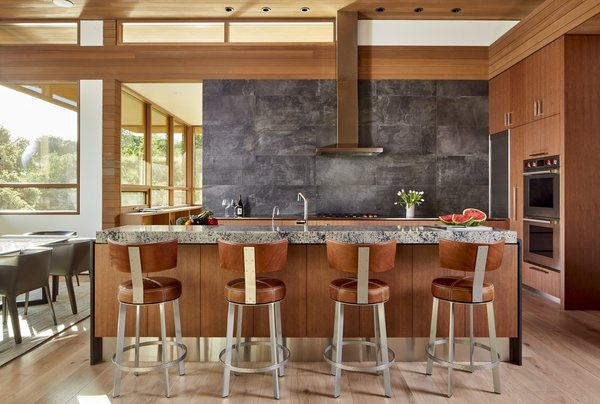 The kitchen is fitted with Dekton countertops by Cosentino, a porcelain tile backsplash by Iris Ecocrete, and custom wood-veneer cabinetry.