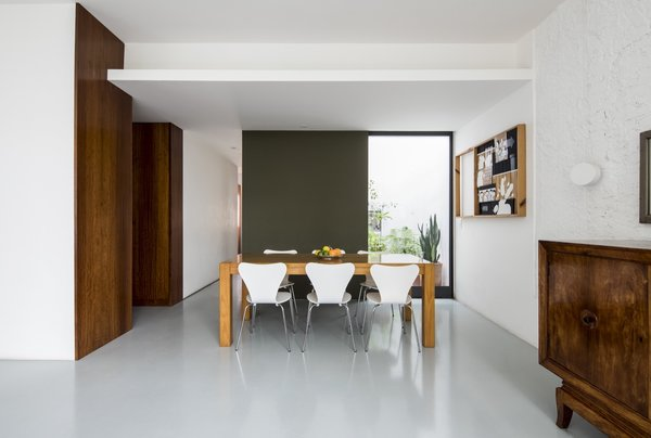 Since the apartment is located on the first level, part of the floor plan was carved out to serve as two ventilation pits for the upper-floor bathrooms and kitchens. The architects strategically decided to turn these spaces into small gardens.