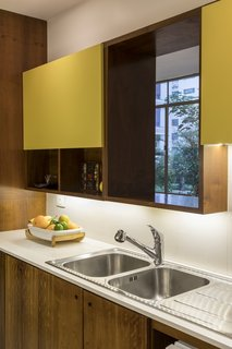 An opening above the double sink frames views of the tree canopy.