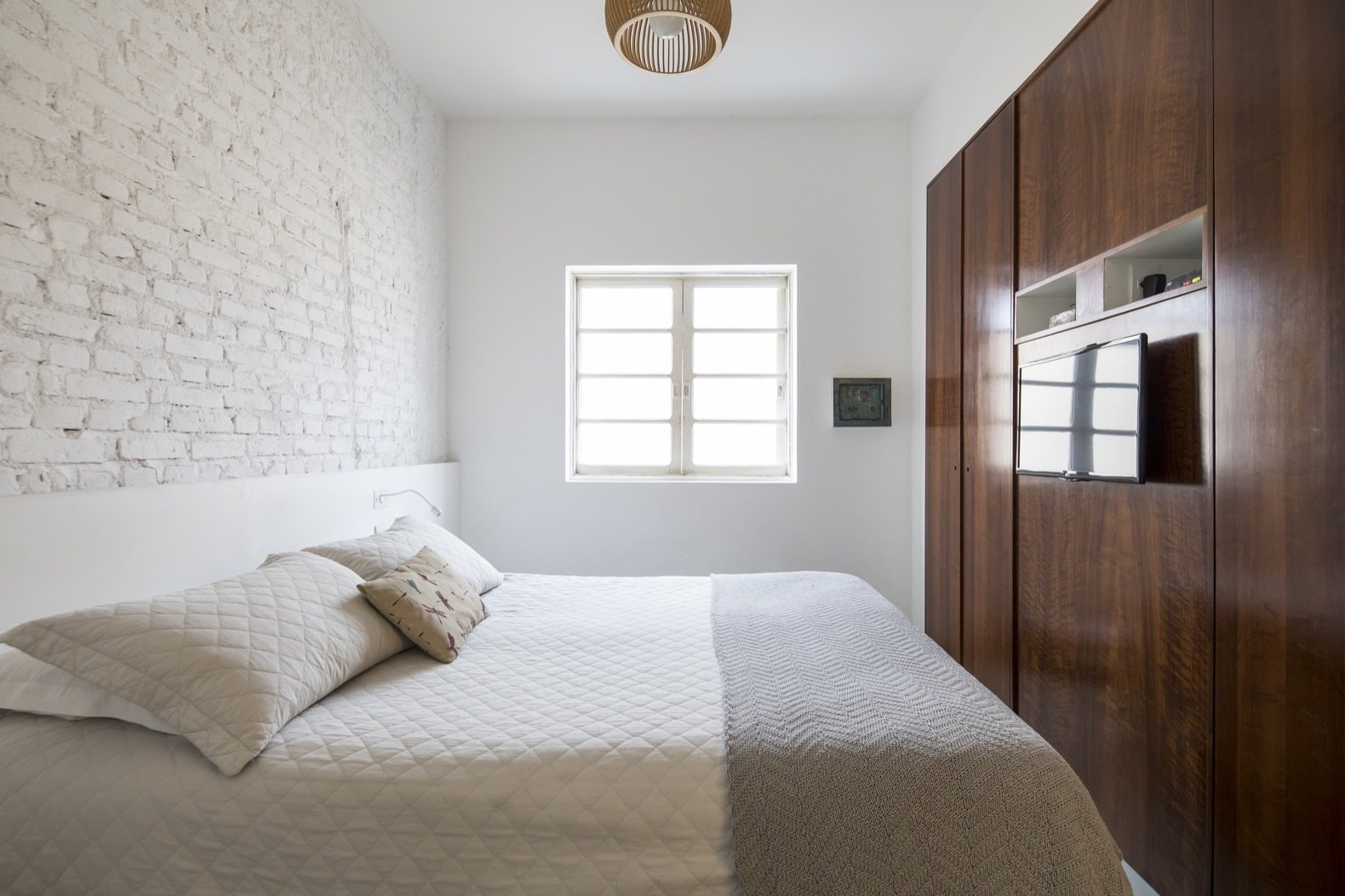 Bedroom, Bed, Dresser, and Ceiling Lighting The perimeter walls have been peeled back to expose the original brick as a reference to the building's past.    Best Photos from Greenery Breathes Fresh Life Into a Brazilian Midcentury