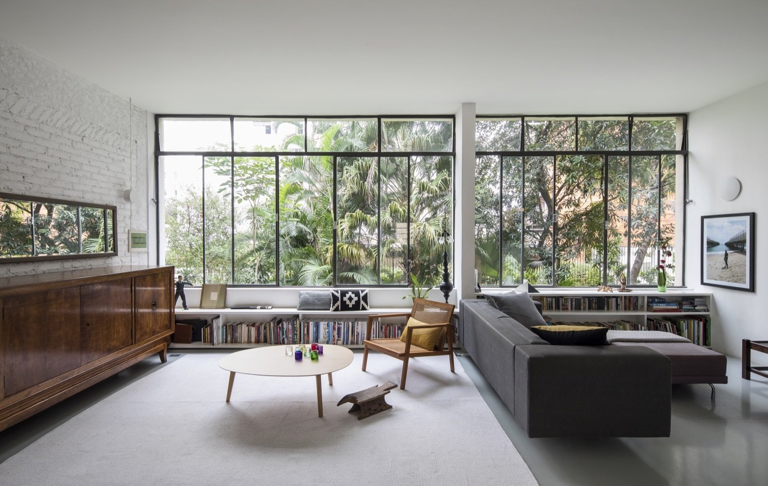Living Room, Sofa, Laminate Floor, Storage, Chair, and Coffee Tables The original steel window frames were restored and now overlook views of a lush canopy.    Photo 2 of 13 in Greenery Breathes Fresh Life Into a Brazilian Midcentury