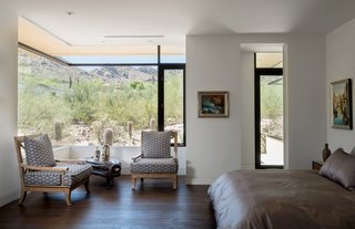 The master bedroom frames sweeping landscape views via a corner window.