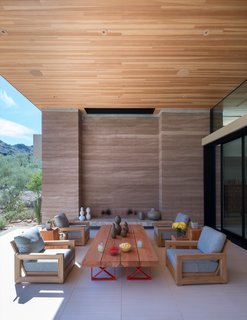 This outdoor room is flanked by rammed earth walls constructed from soil excavated on site.