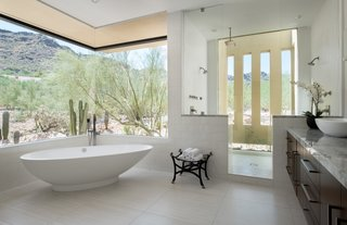 A freestanding soaking tub in the master bath is perfectly placed beneath a corner window shaded by the roof overhang.