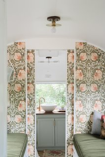 Sliding walls wallpapered with Pimpernell by William Morris separate the bathroom from the lounge/sleeping space.
