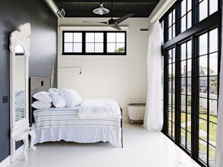 The master bedroom opens up to the wraparound terrace. The Restoration Hardware bed is set against an accent wall that is painted Behr's Cracked Pepper.