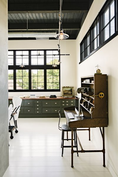 A vintage post office desk anchors one end of the office that's fitted with built-in cabinetry with a 16-foot-long walnut top on the far wall.