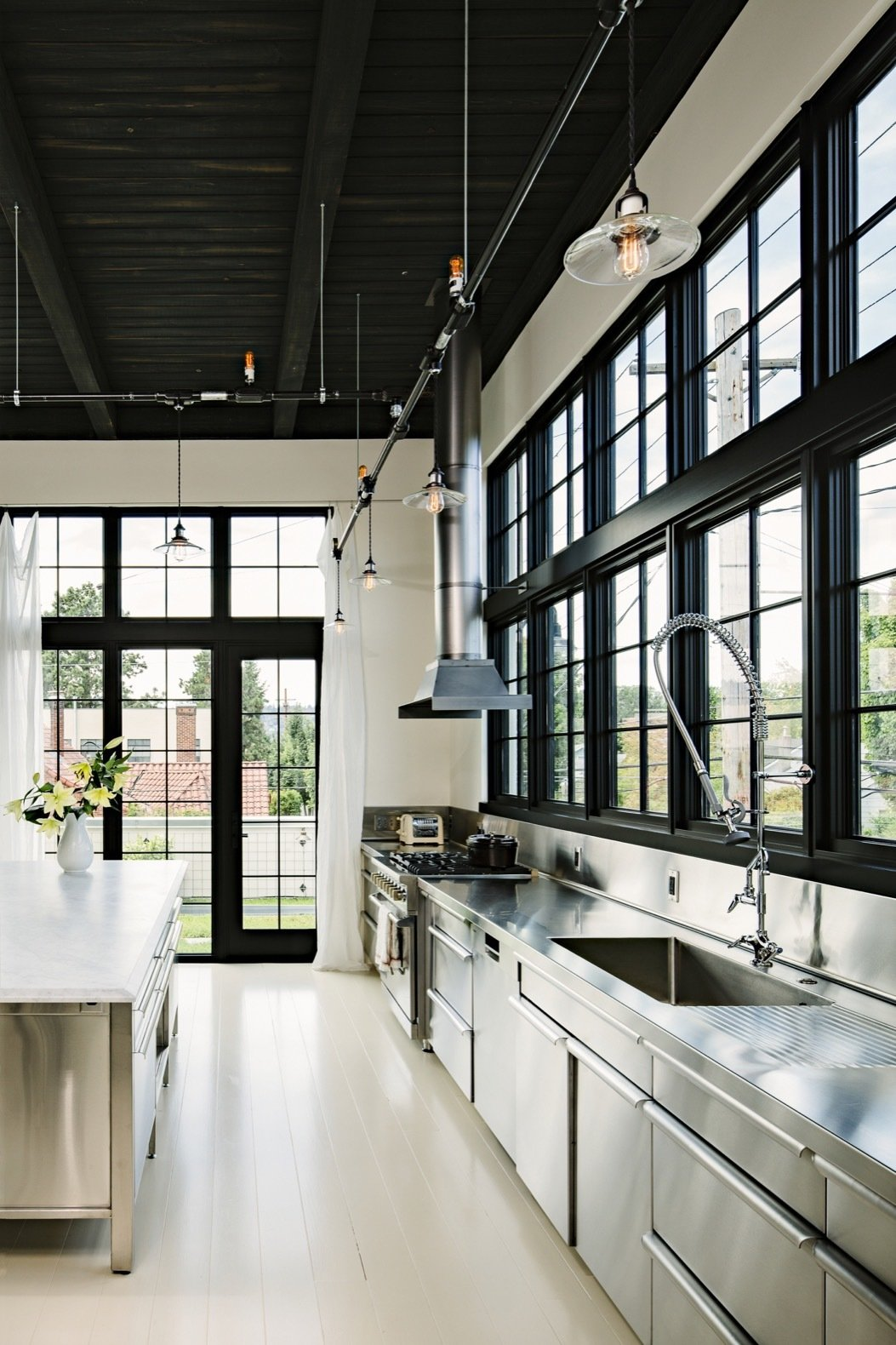 "Kitchen, Painted Wood, Wall Oven, Metal, Pendant, Metal, Cooktops, Range Hood, Refrigerator, Undermount, and Metal To bring their adaptive-reuse abode to life, a pair of former New Yorkers tapped local studio Emerick Architects, which had completed similar renovations, such as the nearby rehabbed Ford Model-T Factory. ""Marrying practicality with craftsmanship, almost everything for the project was handmade locally by Portland artisans including cabinetry, steel work, railings, doors, stairs, light fixtures, and plaster,"" adds the firm. Stainless steel has been used for the kitchen counters, cabinets, and backsplash.  Kitchen Metal Range Hood Photos from A 1920s Portland Warehouse Is Rehabbed Into an Industrial-Chic Home"