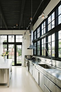 "To bring their adaptive-reuse abode to life, a pair of former New Yorkers tapped local studio Emerick Architects, which had completed similar renovations, such as the nearby rehabbed Ford Model-T Factory. ""Marrying practicality with craftsmanship, almost everything for the project was handmade locally by Portland artisans including cabinetry, steel work, railings, doors, stairs, light fixtures, and plaster,"" adds the firm. Stainless steel has been used for the kitchen counters, cabinets, and backsplash."