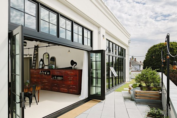 Bi-fold sliding Marvin doors recall steel-framed factory windows, yet are actually built of black-painted wood and insulated glass.