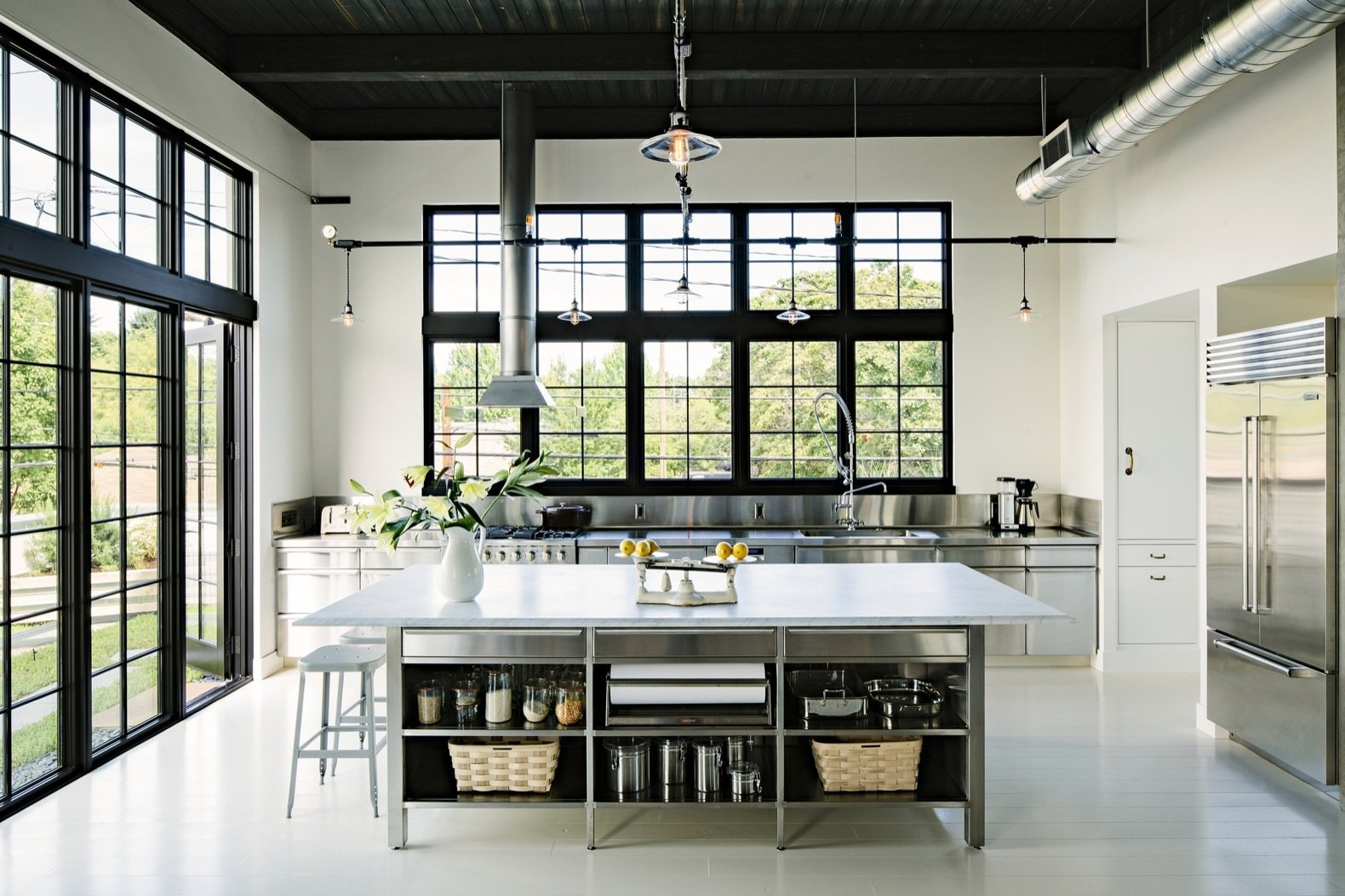 Kitchen, Metal, Cooktops, Metal, Refrigerator, Painted Wood, Pendant, Wall Oven, Range Hood, and Metal The kitchen island is topped with a five-by-10-foot slab of Carrera marble.  Best Kitchen Range Hood Metal Metal Pendant Photos from A 1920s Portland Warehouse Is Rehabbed Into an Industrial-Chic Home