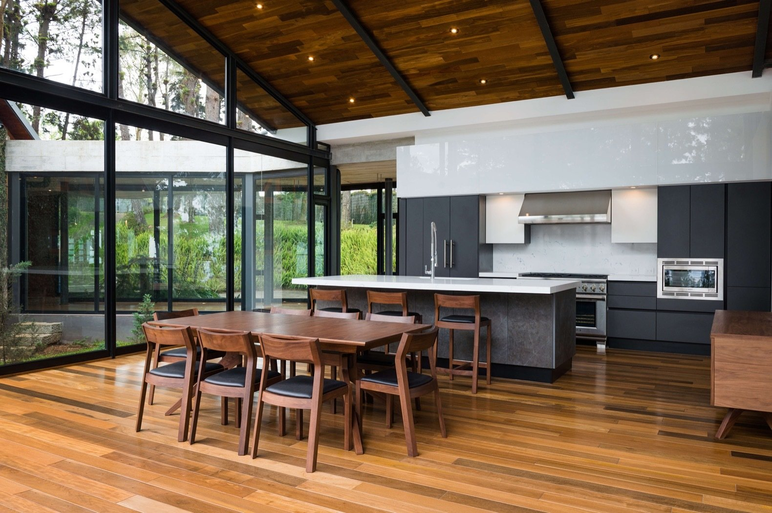 Kitchen, Medium Hardwood Floor, Range, Range Hood, Recessed Lighting, Refrigerator, White Cabinet, and Microwave Full-height glazing floods the interiors with natural light.  Photo 11 of 15 in A Small Guatemalan Hut Gains a Thoughtful Glazed Expansion