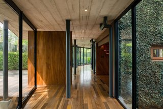 Topped with a thin slab of board-formed concrete, the glazed corridor doubles as the entry foyer.