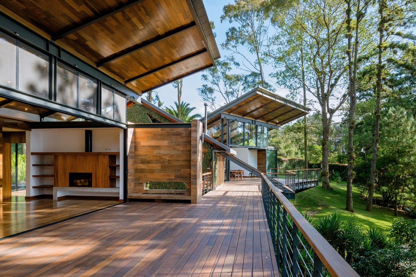 """Outdoor, Wood Patio, Porch, Deck, Large Patio, Porch, Deck, Back Yard, Trees, and Grass """"The retreat has an exterior platform larger than the interior in order to encourage the inhabitants to carry on outdoor activities,"""" says Alejandro. """"The exterior platforms are connected so it is possible to walk around in a cyclic and spontaneous pattern.""""  Photo 10 of 15 in A Small Guatemalan Hut Gains a Thoughtful Glazed Expansion"""