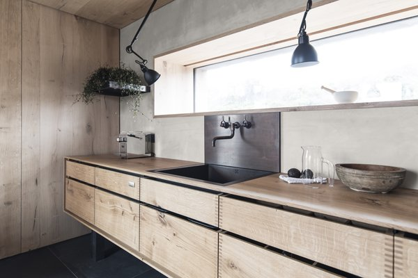 The kitchen has been custom-crafted from Danish oak, a material used throughout the home. A narrow ribbon-window provides panoramic views.
