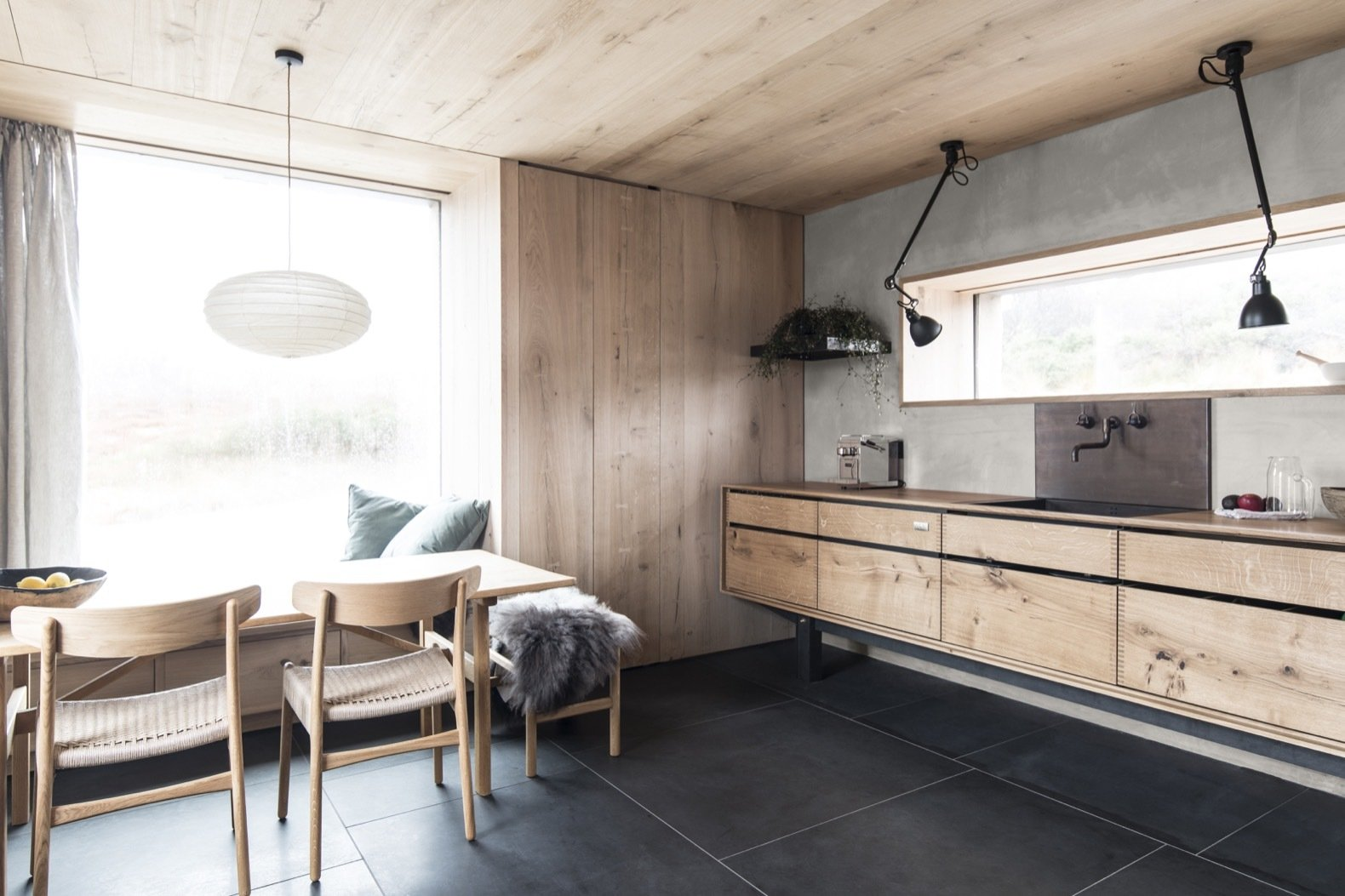 Kitchen, Wood Cabinet, Cooktops, Wood Counter, and Ceiling Lighting A muted and natural material palette of stone, timber, metal, and glass define the interiors. The floors are locally-mined Caithness stone, installed with radiant underfloor heating.  Best Photos from Cozy Up in a Nordic-Inspired Retreat Reborn From Ruins
