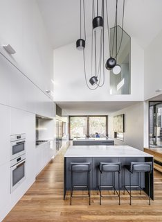 The double-height kitchen includes cabinets finished with two-pack polyurethane, a Corian kitchen countertop, and an island topped with Quantum Quartz.
