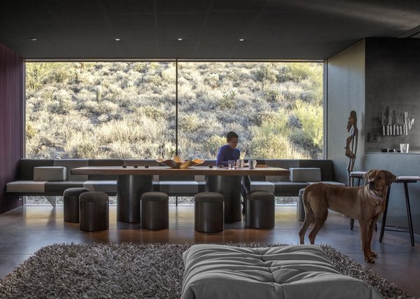 Massive glazing in the communal area frame views of a desert knoll to the north.