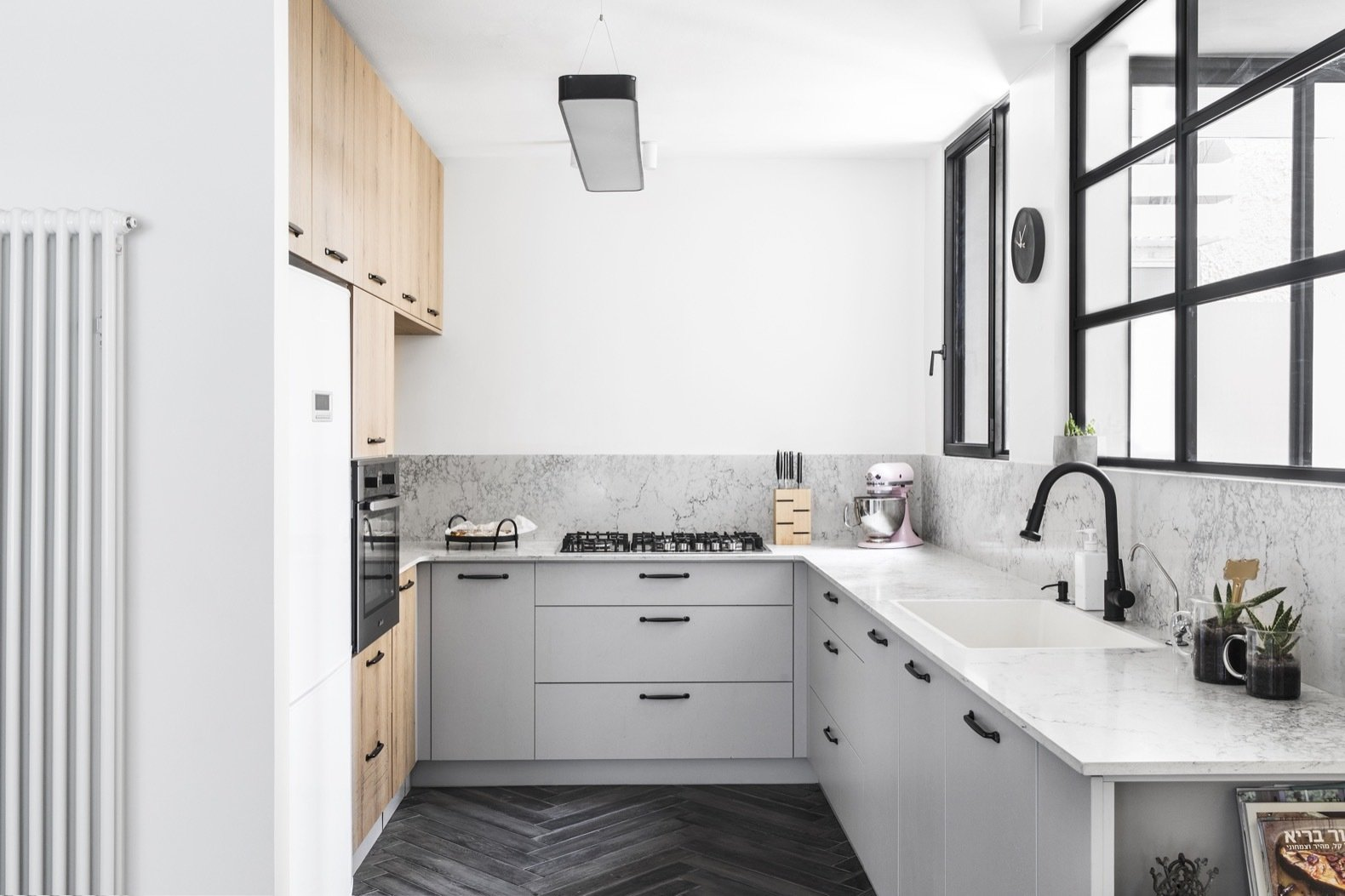 Kitchen, Porcelain Tile, Wall Oven, Ceiling, White, Cooktops, Refrigerator, Drop In, Engineered Quartz, Wood, and Accent Walls were torn down to create a bright, open kitchen.  Best Kitchen Ceiling Wall Oven Wood Accent Cooktops Porcelain Tile Photos from Budget Breakdown: A Stunning Apartment Revamp Mixes High and Low For Under $100K