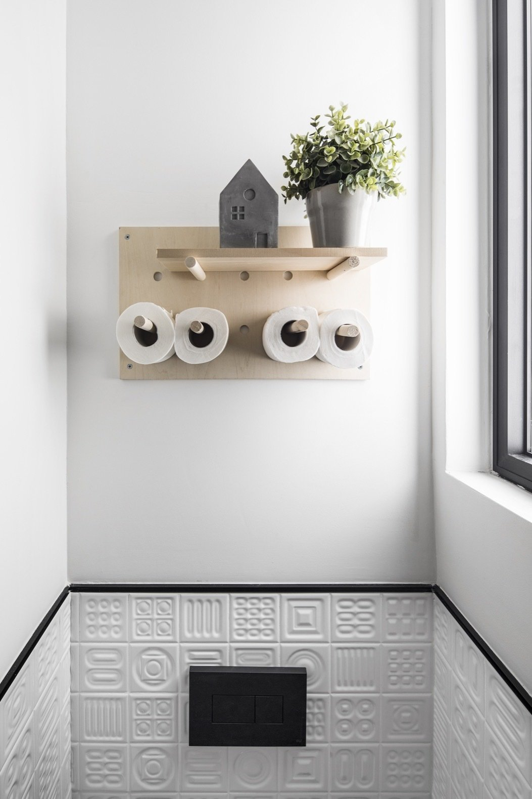 Bath Room, Porcelain Tile Floor, and One Piece Toilet This wooden peg board for the bathroom was Efrat's favorite purchase, which she says was inexpensive yet chic.  Photo 19 of 21 in Budget Breakdown: A Stunning Apartment Revamp Mixes High and Low For Under $100K