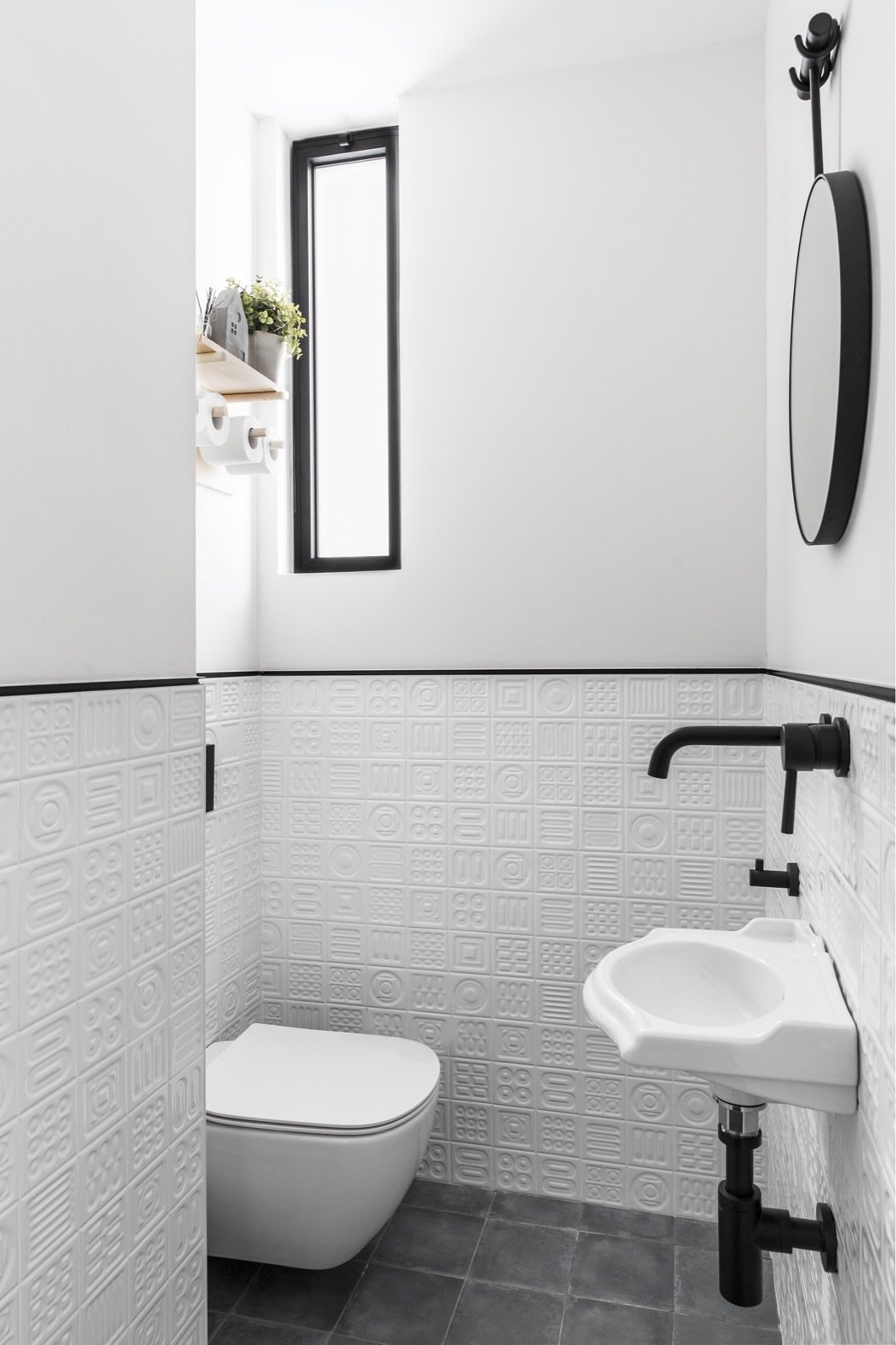 Bath Room, Wall Mount Sink, Porcelain Tile Floor, and One Piece Toilet Lined with black porcelain tiles and complementary black fixtures, the half-bath was given a bright white refresh that instantly makes the tiny room feel more spacious.  Photo 18 of 21 in Budget Breakdown: A Stunning Apartment Revamp Mixes High and Low For Under $100K