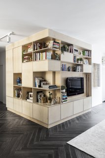 This custom-built timber storage unit serves as a counterpoint to the glass-walled study and injects a sense of honey-hued warmth to a mostly monochromatic palette.