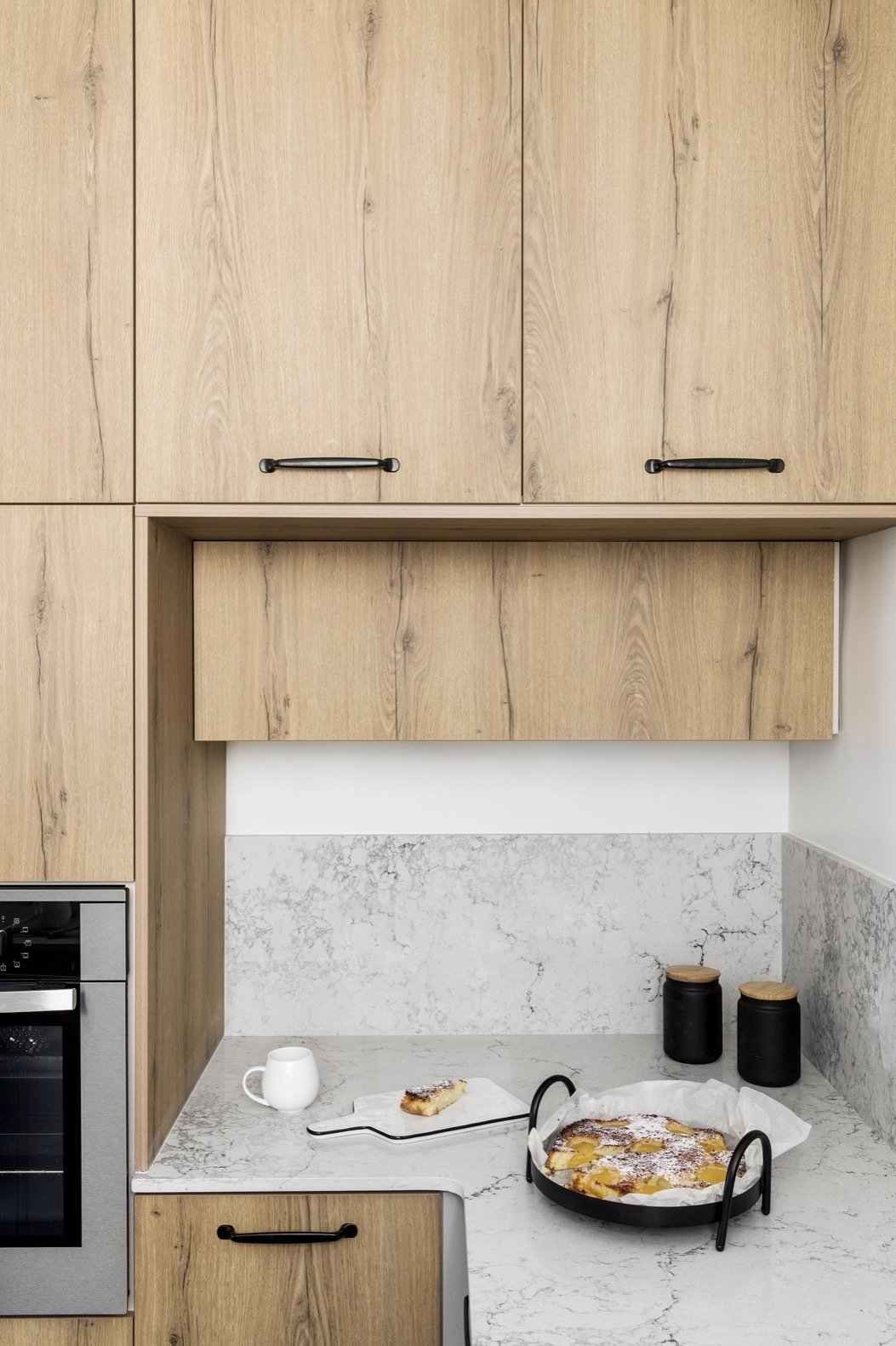 Kitchen, Wall Oven, Engineered Quartz Counter, Porcelain Tile Floor, and Wood Cabinet The kitchen countertops are quartz, and the cabinets are Formica.  Photo 6 of 21 in Budget Breakdown: A Stunning Apartment Revamp Mixes High and Low For Under $100K