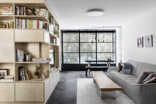 Fitted with a new black-framed window unit, the new, light-filled living room features a sofa and coffee table from Beitili.