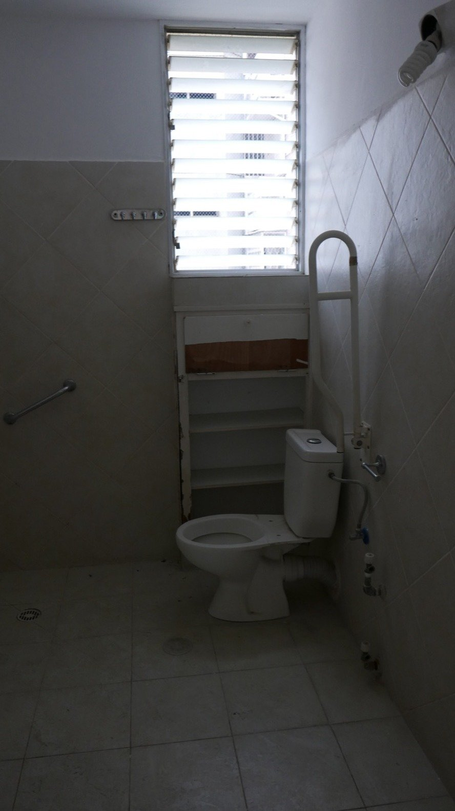 Bath Room and Two Piece Toilet Before: the master bathroom felt small and dark.  Photo 12 of 21 in Budget Breakdown: A Stunning Apartment Revamp Mixes High and Low For Under $100K
