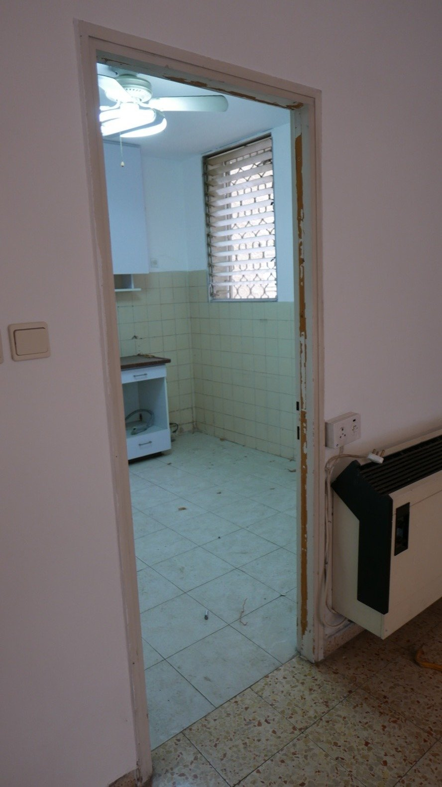 Kitchen and White Cabinet Before: the dated kitchen had been enclosed by walls and felt very dark, even in daytime.  Photo 4 of 21 in Budget Breakdown: A Stunning Apartment Revamp Mixes High and Low For Under $100K
