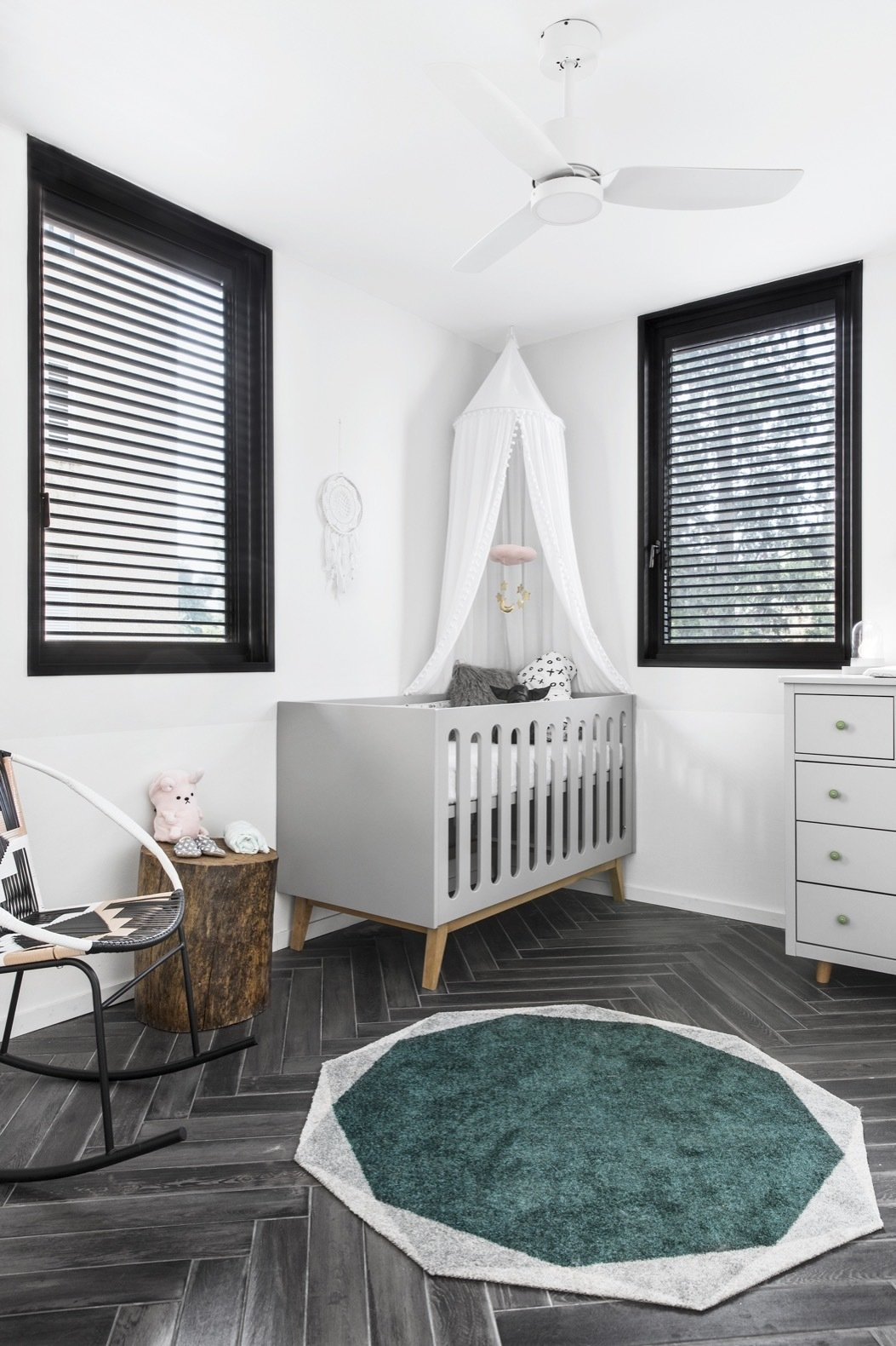 Bedroom, Ceiling Lighting, Rockers, Bed, Porcelain Tile Floor, Rug Floor, Storage, and Night Stands The second bedroom has been converted into a nursery.   Photo 16 of 21 in Budget Breakdown: A Stunning Apartment Revamp Mixes High and Low For Under $100K