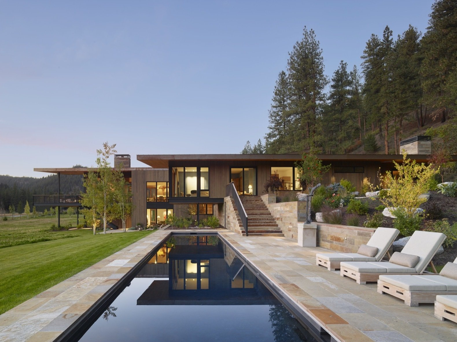 Outdoor, Trees, Stone Patio, Porch, Deck, Large Patio, Porch, Deck, Side Yard, Large Pools, Tubs, Shower, and Grass A large pool is located on the east side of the residence.   Photo 10 of 12 in A Modern Montana House Mixes a Love of Art With the Outdoors