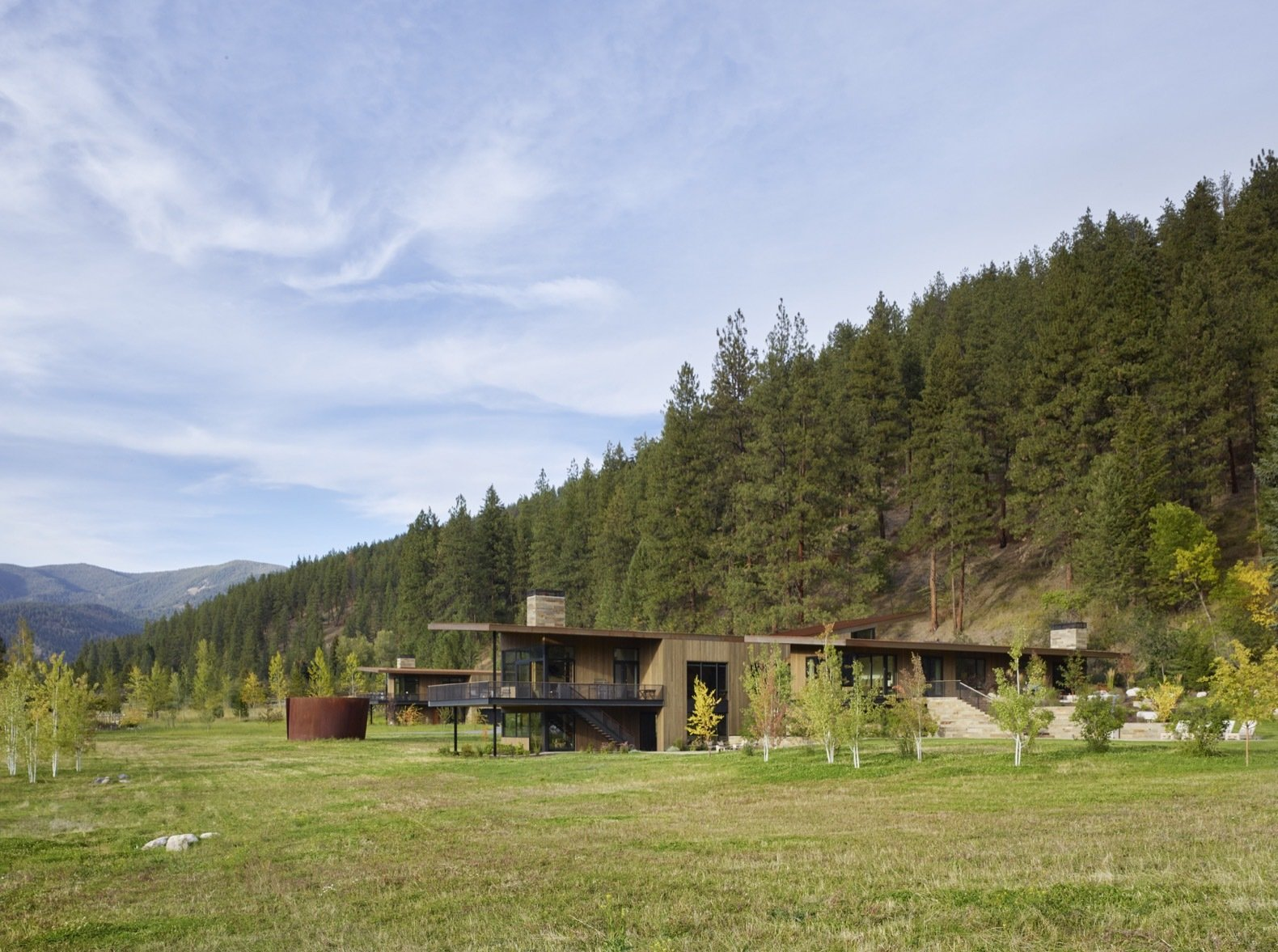 Exterior, Metal Roof Material, Wood Siding Material, House Building Type, Stone Siding Material, Glass Siding Material, and Metal Siding Material The modern Montana home is nestled into a transitional zone between a forested butte and a grassy meadow in the western part of the state.    Photo 1 of 12 in A Modern Montana House Mixes a Love of Art With the Outdoors