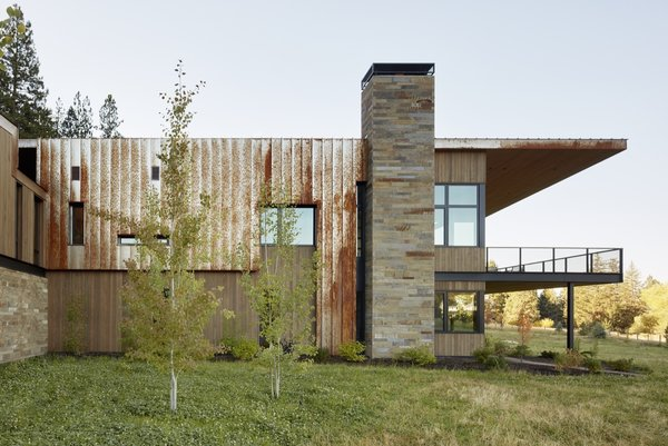 The residence is clad in a combination of vertical grain cedar, Firestone aluminum, and Corten standing-seam metal. The stone is Frontier Sandstone.