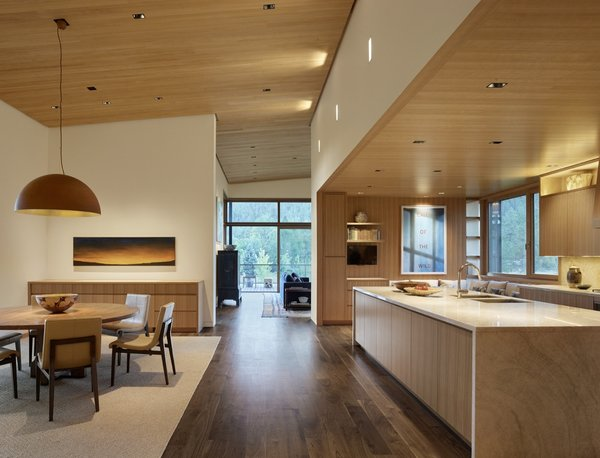 The open kitchen is fitted with Perla Venato Quartzite countertops and timber cabinetry.