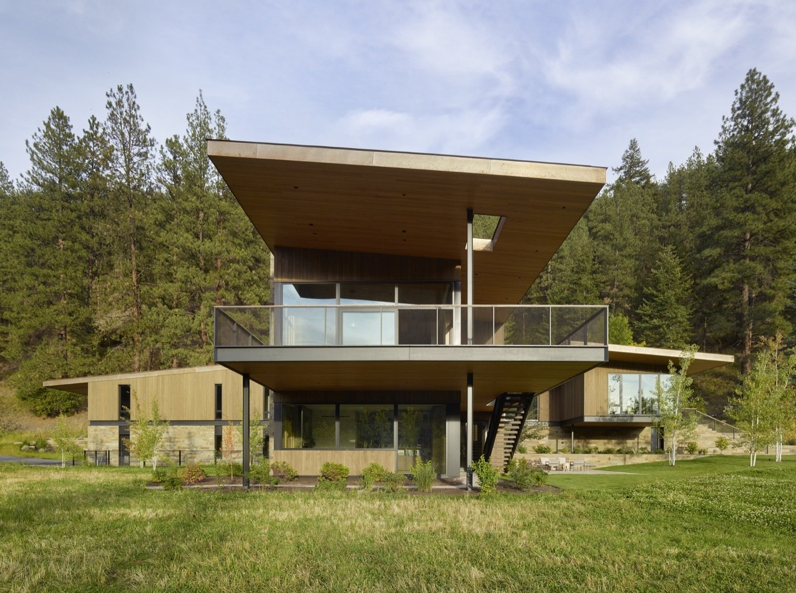 Exterior, House Building Type, Metal Roof Material, Wood Siding Material, Stone Siding Material, and Metal Siding Material The spacious second-story terrace projects toward the south to overlook views of the meadow.    Photo 8 of 12 in A Modern Montana House Mixes a Love of Art With the Outdoors