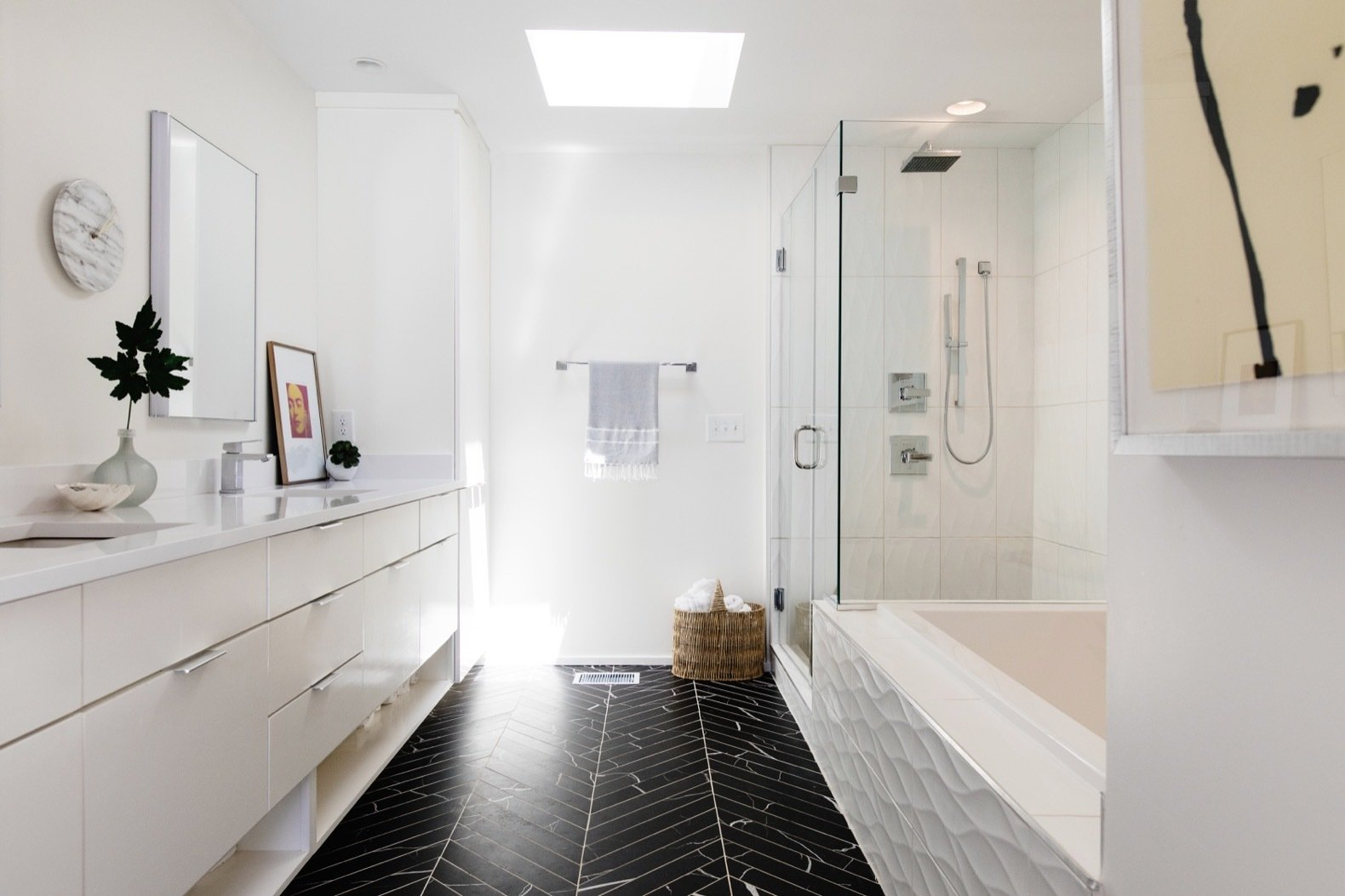 Bath, Enclosed, Recessed, Alcove, Undermount, Porcelain Tile, Soaking, Engineered Quartz, and Corner Marble-like, porcelain tile laid in a herringbone pattern gives the master bath a luxurious feel.  Best Bath Enclosed Alcove Photos from Before & After: A Nashville Midcentury Now Gleams With Natural Light
