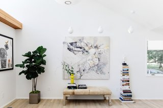 White walls, natural light, and a neutral color palette provide an ideal setting for displaying the owners' art collection.