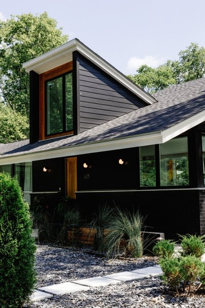 """We bumped up the roof line in two spots to create dramatic ceilings in the living area and flood the rooms with light,"" explains Hannah. ""The brick and hardboard were then painted black, and we added cedar siding to add depth."""