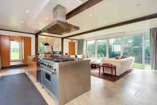The 12-foot-long kitchen island is fitted with a Miele dishwasher, a Viking range, and custom wooden cabinets.