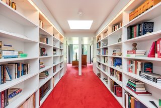 The main landing on the second floor of the West Wing is defined by a built-in library with recessed lighting.