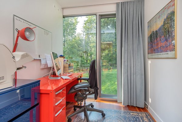 Featured here is one of this shipping container home's two private office spaces, which incorporates office furniture clad in bright colors. These make great modern home office ideas if you're going for an industrial look.