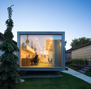 The floor-to-ceiling, triple-glazed wall overlooks the lawn and residence.