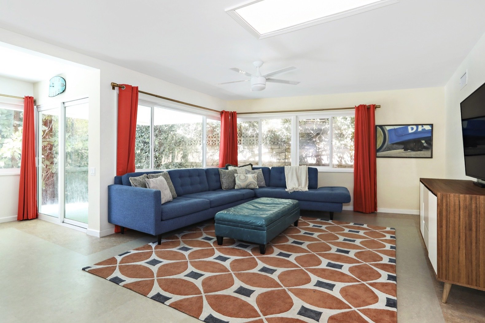 Living Room, Terrazzo Floor, Ceiling Lighting, Media Cabinet, Sectional, and Ottomans Flooded with natural light, the media room is located to one side of the open kitchen.   Photo 3 of 11 in Own Comedian Adam Carolla's Renovated L.A. Midcentury For $3.4M