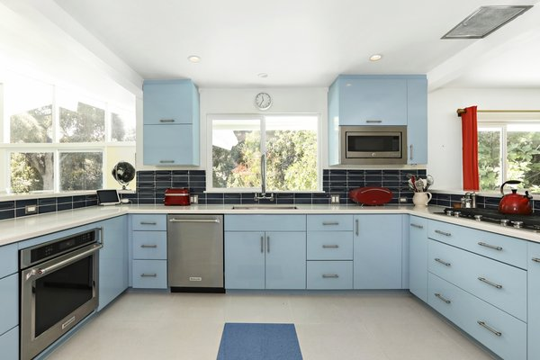 Walls were knocked down to create an open chef's kitchen fitted with retro blue cabinetry complemented by a dark blue tile backsplash.