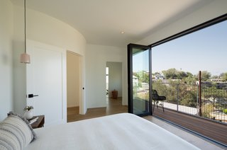 The master suite is located in the front of the home and opens up to a balcony through folding glass doors.