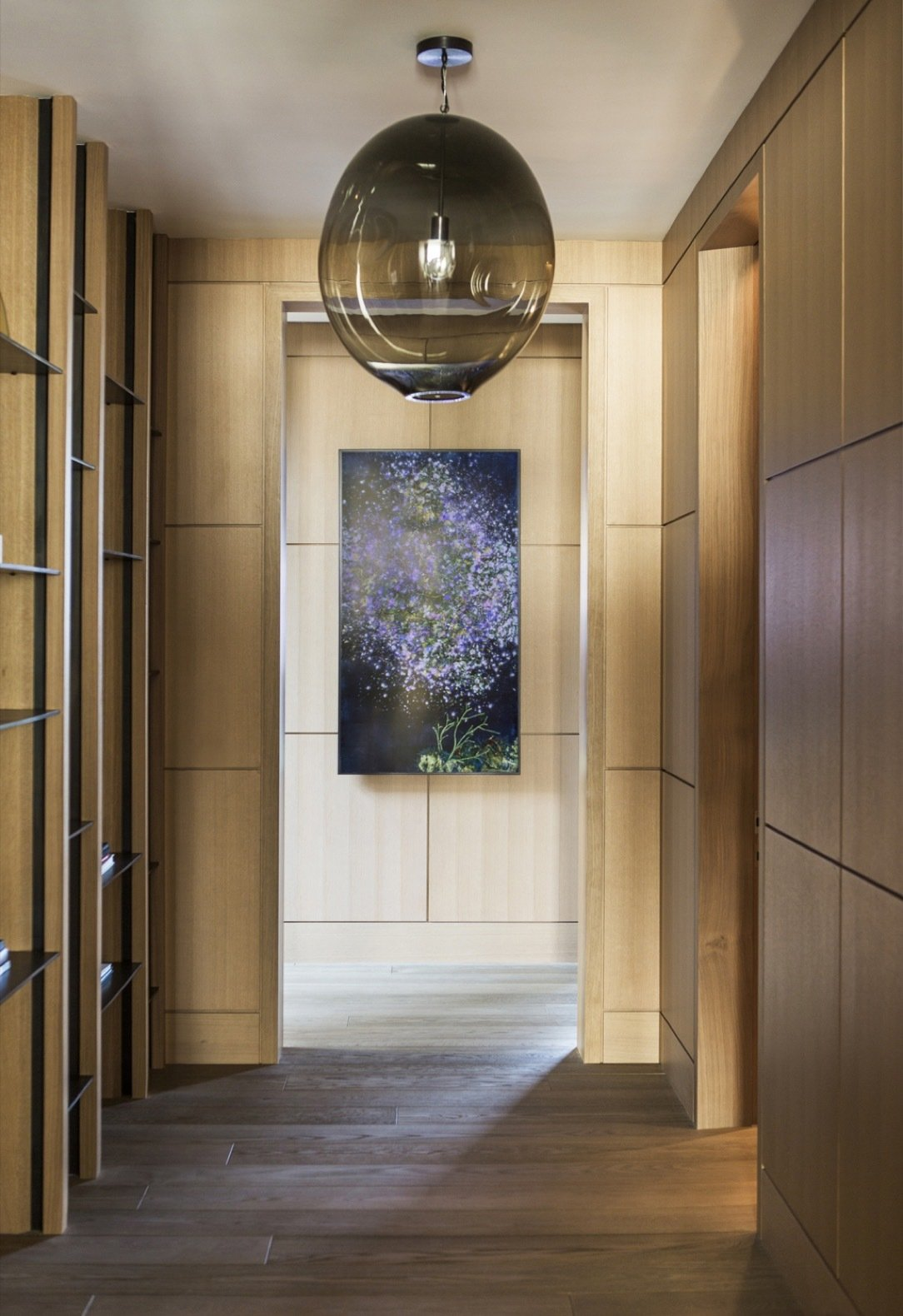 Hallway and Medium Hardwood Floor Rift-sawn European white-oak wall paneling and engineered European oak flooring lend warmth to the modern home.   Photo 6 of 14 in An Energy-Conscious Home Gets Woven Into a Waterfront Landscape