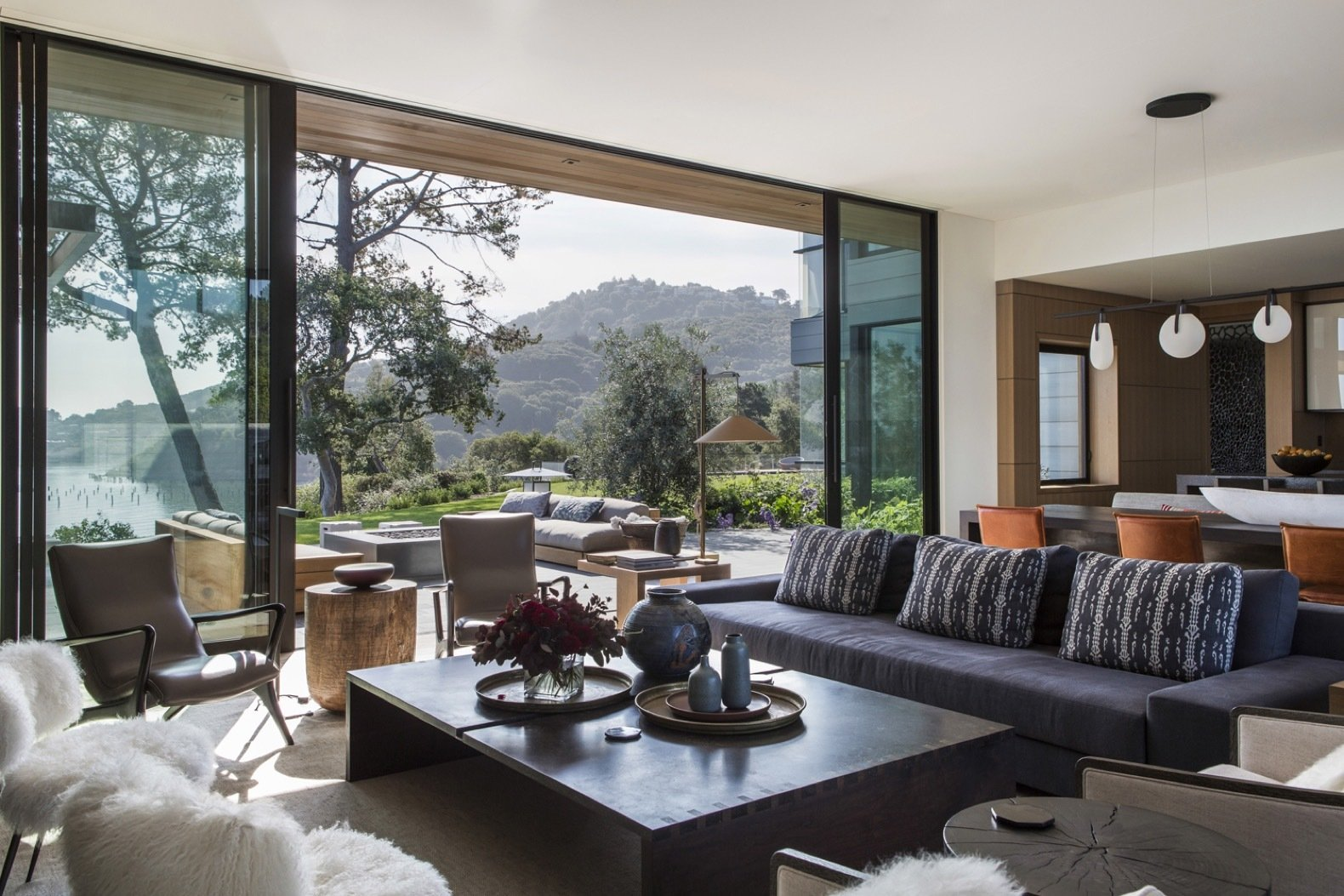 Living Room, Sofa, Medium Hardwood Floor, Pendant Lighting, Chair, and Coffee Tables In the open great room, large sliding glass doors from Fleetwood Windows & Doors blur the boundary between indoors and out.  Photo 8 of 14 in An Energy-Conscious Home Gets Woven Into a Waterfront Landscape