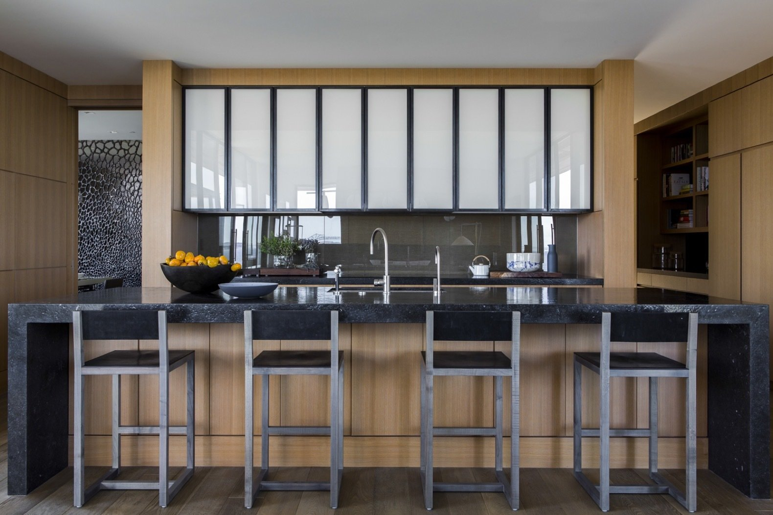 Kitchen, Granite Counter, White Cabinet, Cooktops, Wood Cabinet, Medium Hardwood Floor, and Undermount Sink BDDW bar stools are combined with a waterfall-edge Aged Petite Granit kitchen island.   Photo 14 of 14 in An Energy-Conscious Home Gets Woven Into a Waterfront Landscape