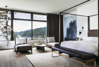 Bathed in natural light, the master bedroom with a Holly Hunt walnut bed commands impressive views of the bay. The hanging art is by Kibong Rhee.